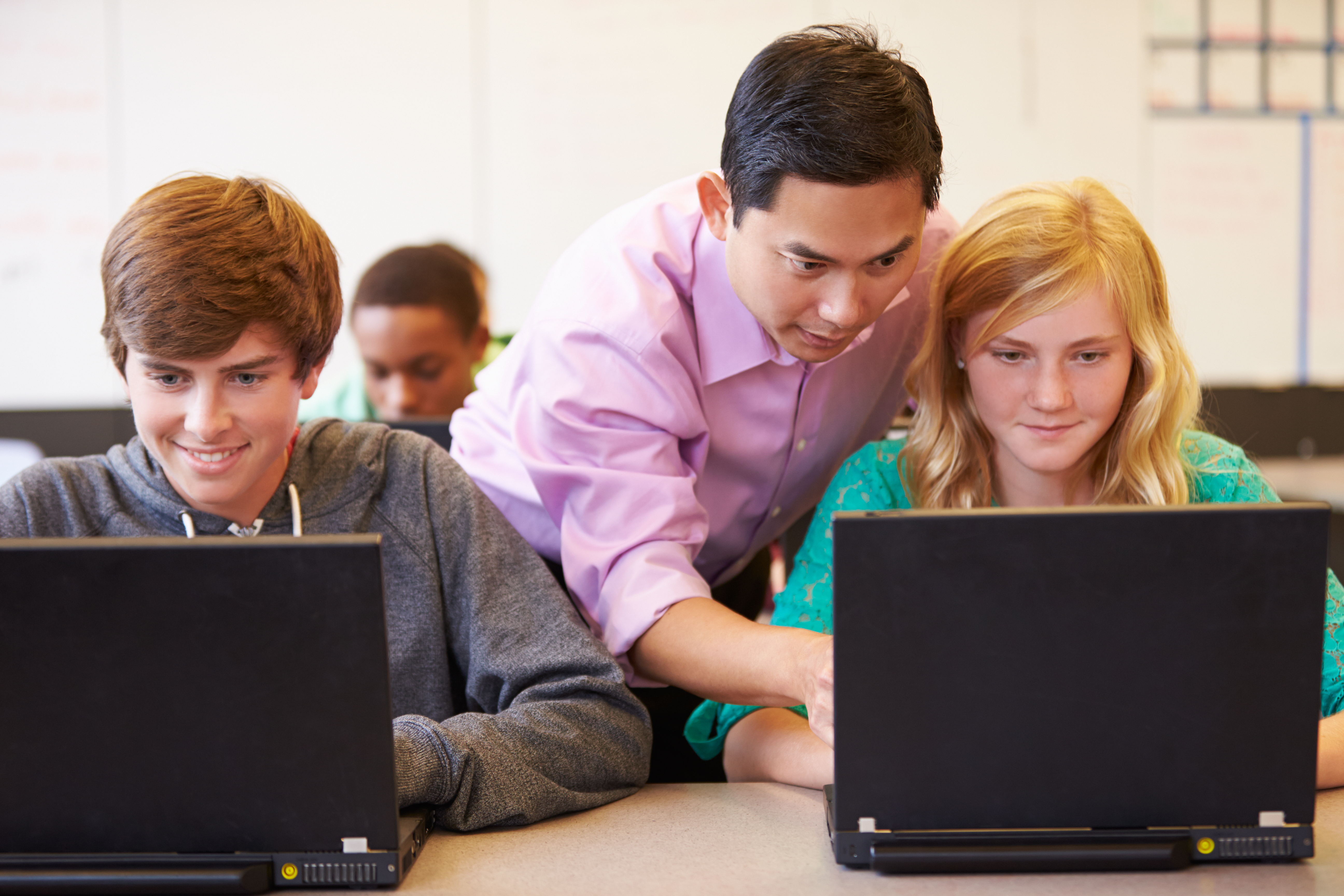 Teacher helping two students on their laptops